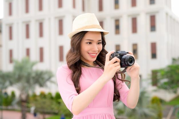 사진 작가의 카메라 여행 사진과 함께 아시아의 도시에서 즐거운 시간을 보내는 예쁜 젊은 여성의 야외 여름 웃는 라이프 스타일 초상화
