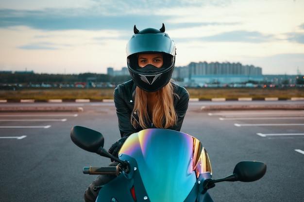 安全オートバイのヘルメットと夜の乗車の準備ができて革のジャケットを身に着けている美しい幸せな若い女性の屋外の夏の肖像画