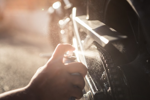 야외 태양은 유지 보수를 위해 오토바이 체인에 스프레이 오일을 바르는 손의 사진을 반영합니다.