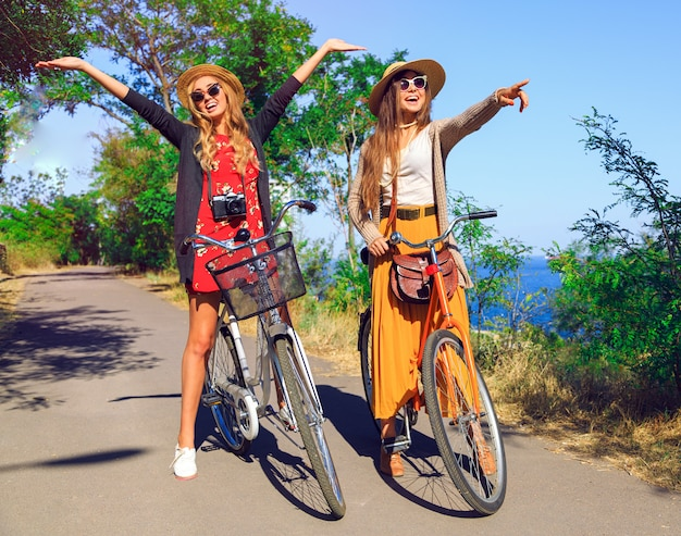 Outdoor sunny fashion portrait of two pretty funny girls, having fun together and going crazy, riding vintage hipster bikes, waring vintage clothes hats and sunglasses. positive mood.