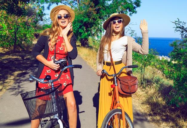 Ritratto di moda soleggiata all'aperto di due ragazze piuttosto divertenti, che si divertono insieme e impazziscono, in sella a biciclette vintage hipster, indossando cappelli e occhiali da sole. stato d'animo positivo.