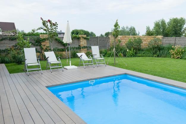 Открытый бассейн на частной резиденции, газон, сад.