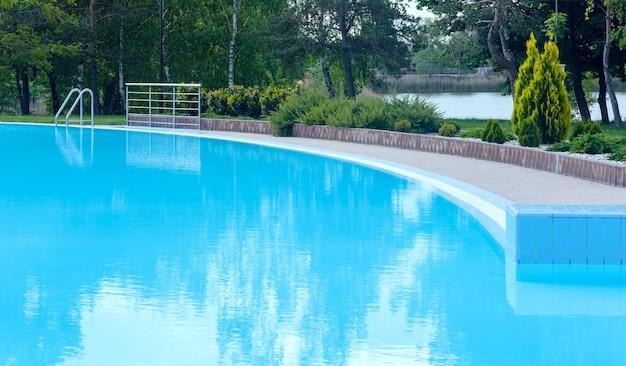 Вид на открытый бассейн с отражением дерева на поверхности воды.