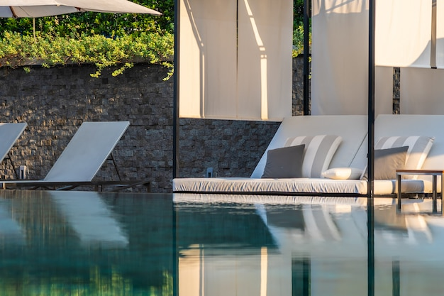 Outdoor swimming pool with umbrella chair lounge around there for leisure travel