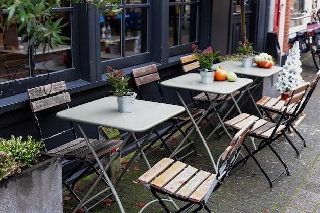 Уличные столы со стульями на террасе кафе в амстердаме. винтажная европа, новогодние праздники в стиле ретро. уличное кафе во время рождества с тыквами и цветами red skimmia на открытом воздухе в европейском стиле.