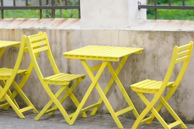 黄色い椅子のある屋外テーブル。通りのカフェ