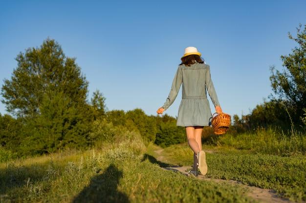 Outdoor teen girl with basket strawberries, straw hat