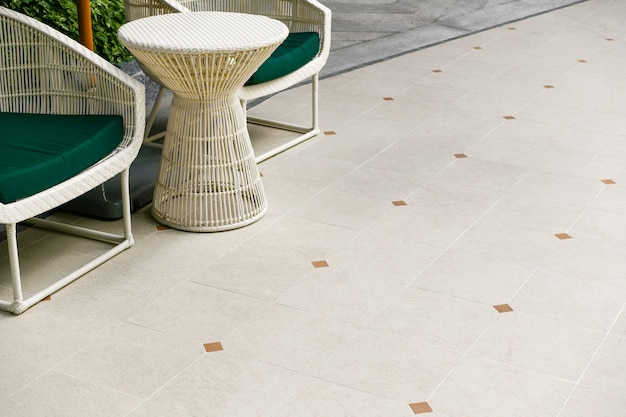 Outdoor terrace area with beige floor tile with sitting area. ceramic granite tile fooring. garden decoration.