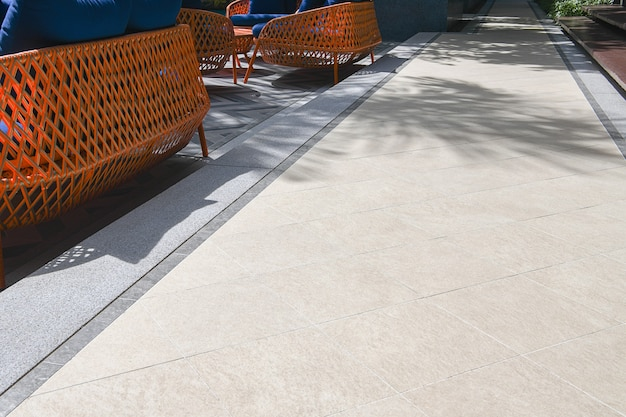 ベージュの床タイルとシッティングエリアのある屋外テラスエリア。パターンと屋外の花崗岩の床。