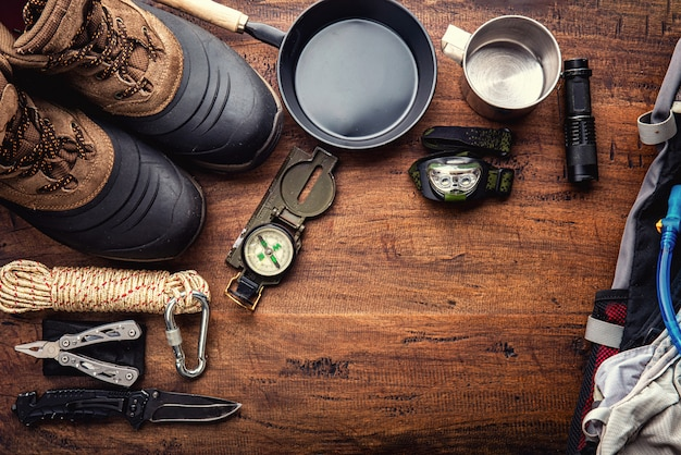 Outdoor travel equipment planning for a mountain trekking camping trip on wooden background