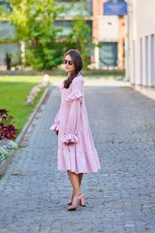 Outdoor urban portrait of young beautiful stylish girl in oversized pink dress