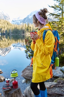 Outdoor vertical shot of pensive female hicker holds hot beverage in teacup, makes drink on special tourist equipment