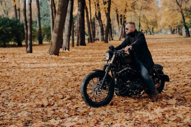 Outdoor view of active male motorcyclist rides bike, wears trendy sunglasses and black jacket