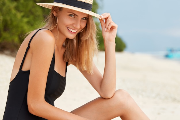 Outdoor view of excited happy young woman wears black swimsuit and hat, being in good mood after swimming in ocean, enjoys freedom and calm atmosphere at beach, sunbathes during hot summer weather