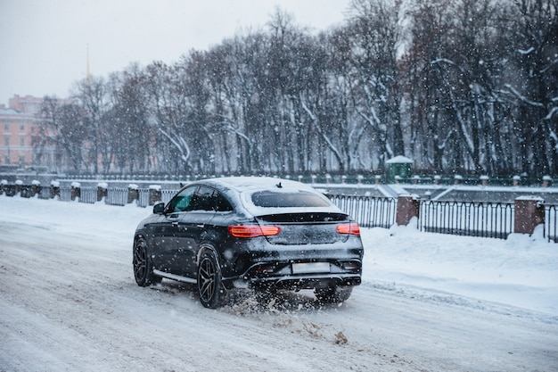 Outdoor view of fast car rides on snowy road on bridge, during cold winter day. snowfall in city
