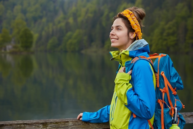 Outdoor view of happy active female wanders near lake and green forest