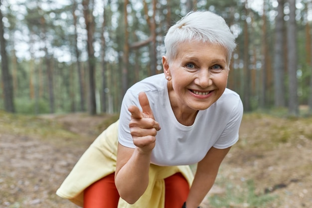 스포츠 옷을 입고 정력적 인 즐거운 여성 연금의 야외보기, 앞으로 기울고 웃고 앞쪽의 앞 손가락을 가리키는