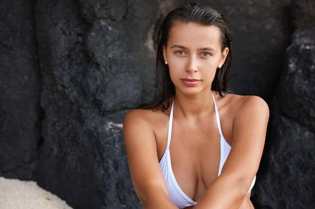 Vista esterna di una signora bagnata dall'aspetto piacevole con un bel seno