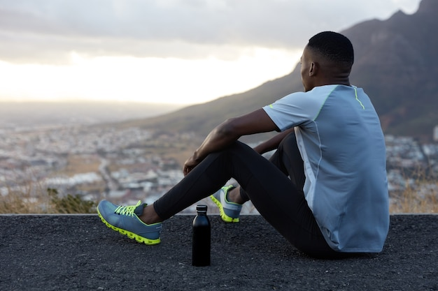 Outdoor view of relaxed african american man with dark healthy skin, drinks water, sits at hill, ejoys beautiful landscape, calm atmopshere, mountains, dressed in clothes for sport. wellness