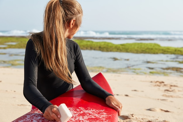 Outdoor view of traveler focused back on ocean, poses on sandy beach