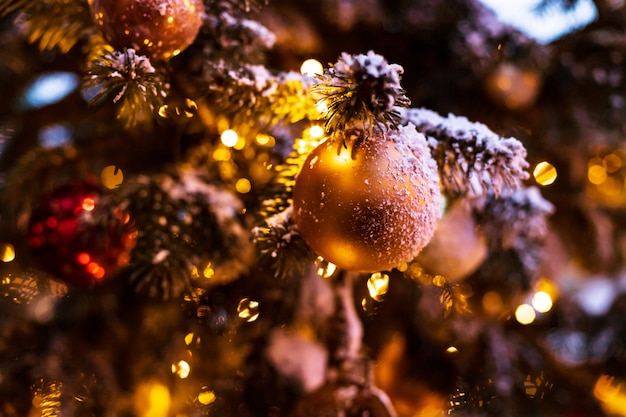 Outdoor vintage decorated christmas tree with light garland, selective focus