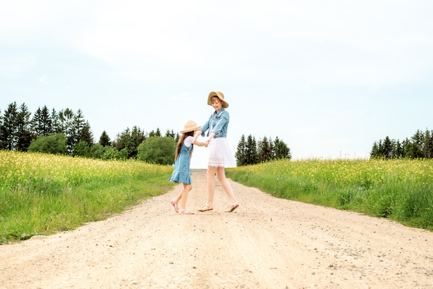 Outdoor walk. summer in field. mother throws up and spinsdaughter on hands on nature,summer day vacation.
