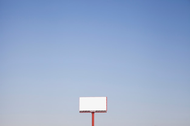 An outdoor white hoarding against blue sky