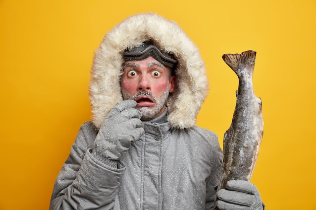 Outdoor winter activities and hobbies concept. stupefied man with red frozen face stares bugged eyes holds caught big fish dressed in warm clothing has successful fishing.