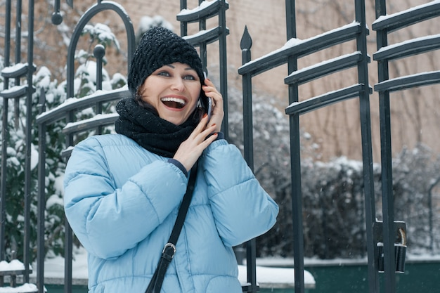 Outdoor winter portrait of mature woman with mobile phone