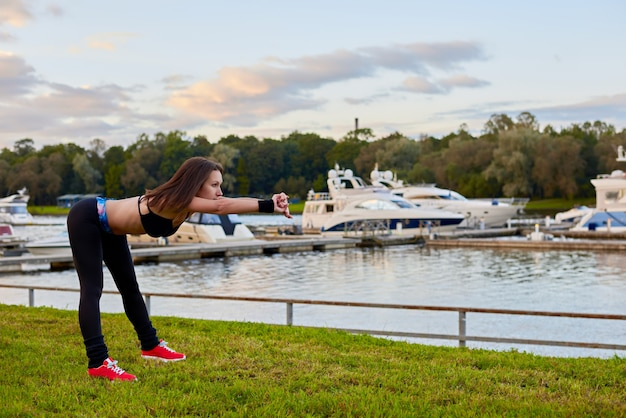 Outdoor workout on beach in evening time. close up portrait of athletic woman, who making sport exercises for healthy life.