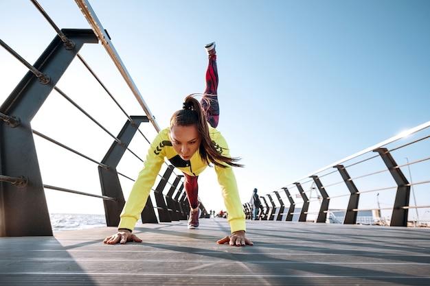 屋外トレーニングのコンセプト。トラックスーツの若い女性が桟橋でスポーツトレーニングを実行します