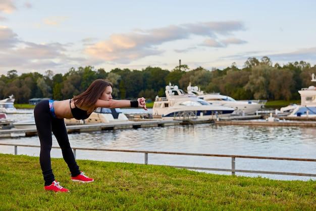 夕方のビーチでの屋外トレーニング。健康的な生活のためにスポーツエクササイズをしている運動女性の肖像画をクローズアップ。