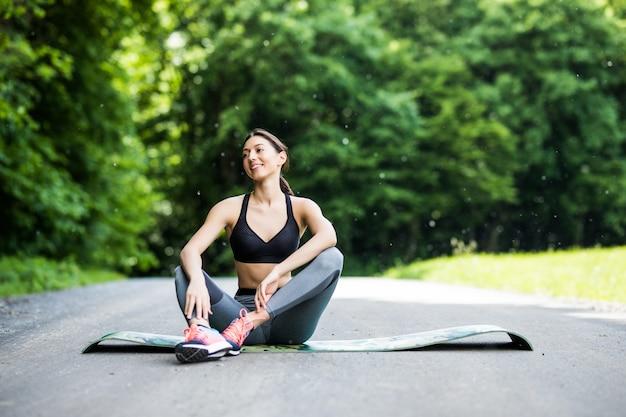 Женщина тренировки на открытом воздухе. фитнес женщина-бегун, сидящая после тренировки на улице в парке