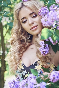 Outdoor young woman surrounded lilac flower summer