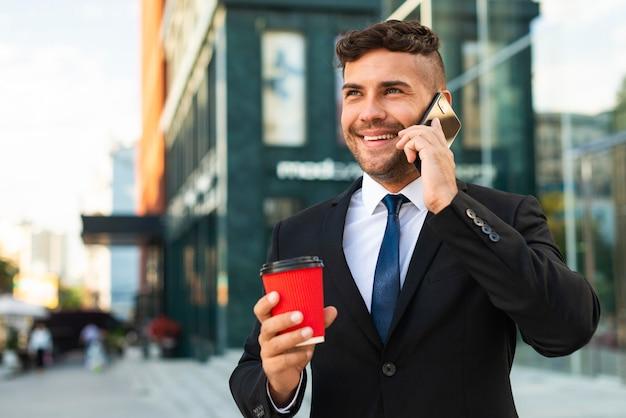 Деловой человек на открытом воздухе пьет кофе и разговаривает по телефону