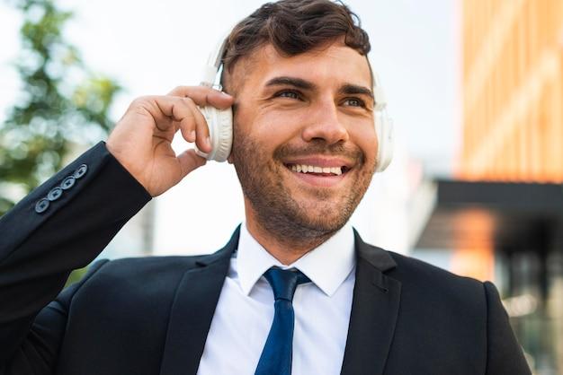 Uomo d'affari all'aperto ascoltando musica felice