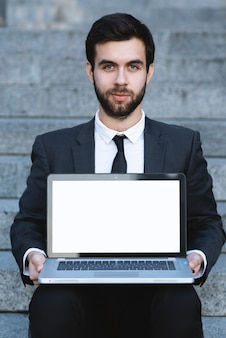 Outdoors businessman sitting on the steps with a laptop on his lap and looking forward.
