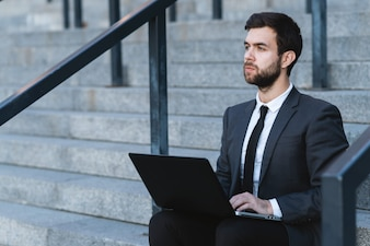 Outdoors businessman sitting on the steps with a laptop on his lap