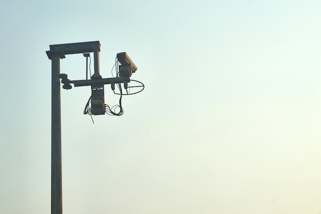 Outdoors circuit camera at road or toll way by officer or police for security on blue sky background