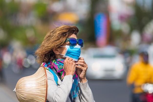 Женщина нося санитарную маску outdoors в центре города вьетнама da lat. медицинская маска защиты от риска появления нового коронирусного вируса ковид-19 в азии