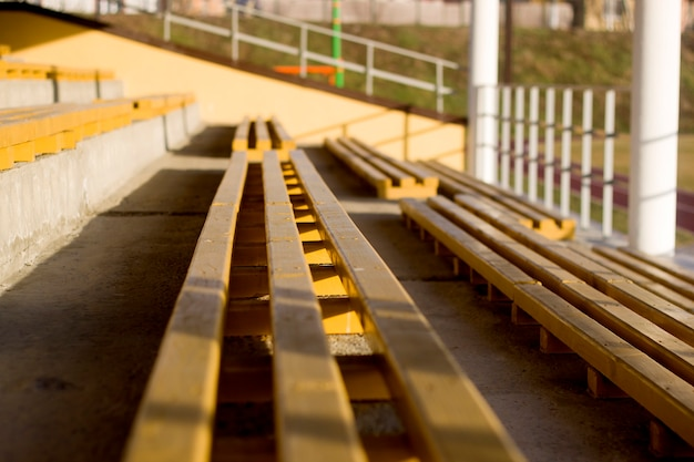 Outdoors gymnasium or stadium section, yellow painted wooden empty benches on sunny summer day. sport and recreation concept.