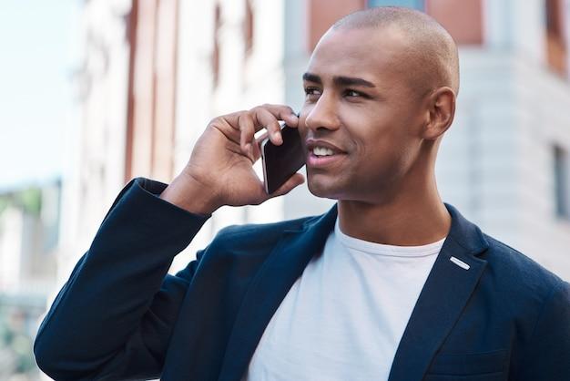 笑顔を脇に見てスマートフォンで話している街の通りに立っているアウトドアレジャー青年