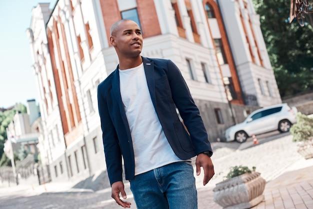 好奇心旺盛な笑顔を脇に見ながら街の通りを歩くアウトドアレジャー青年