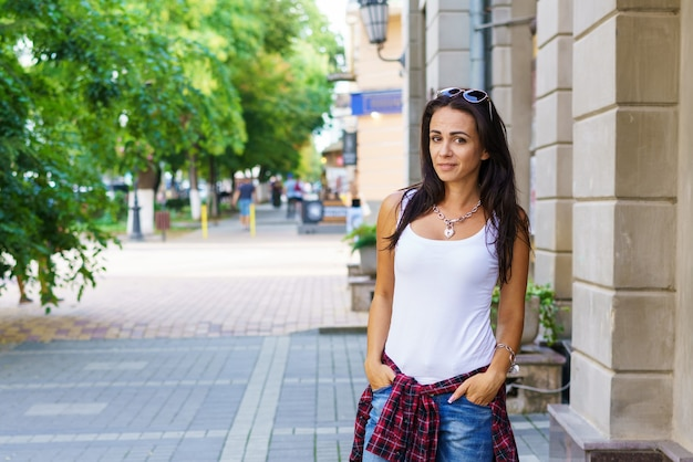 Outdoors lifestyle fashion portrait of contented young woman sitting outdoors. wearing blue jeans and a white t-shirt, smiling, looking happy and enjoying life