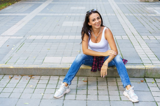 Outdoors lifestyle fashion portrait of contented young woman sitting outdoors wearing blue jeans and...