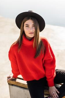 ベンチに座っているかわいい笑顔の赤い髪の少女のアウトドアライフスタイルファッションの肖像画