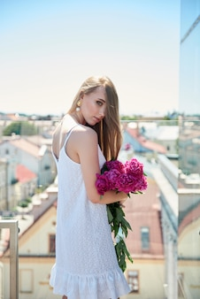 屋根の上を歩いて美しいブロンドの女性のアウトドアライフスタイルファッションの肖像画。街並みを眺める。スタイリッシュなドレスを着て、花を手に。夏の時間