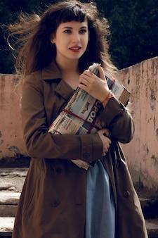 見事なブルネットの女の子のアウトドアライフスタイルファッションの肖像画。街の通りを歩いています。買物に行きます。スタイリッシュなグリーンのフィットコート、ジーンズのスカートを着ています。トレンディなヴィンテージの女性。