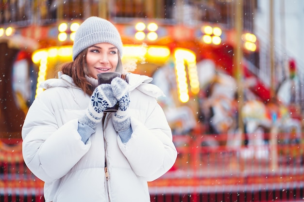 Outdoors lifestyle fashion portrait of stunning woman walking on the holiday city. smiling, drinking coffee and enjoying life. festive mood