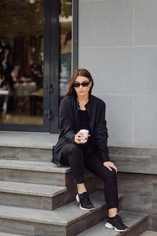 멋진 갈색 머리 여자의 야외 라이프 스타일 초상화. 커피를 마시고 도시 거리를 걷습니다.